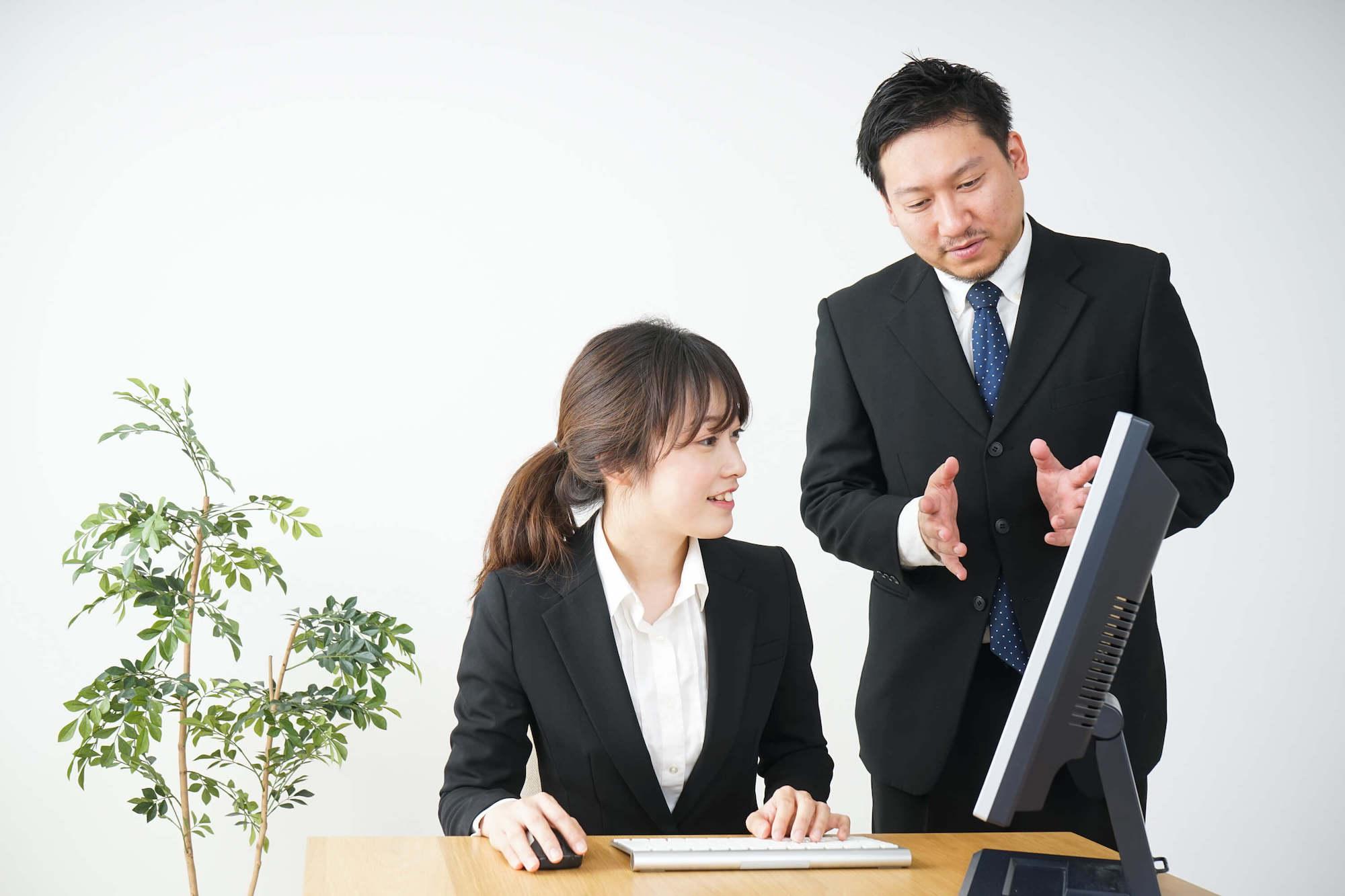 PCを前に講習を受ける女性と男性講師