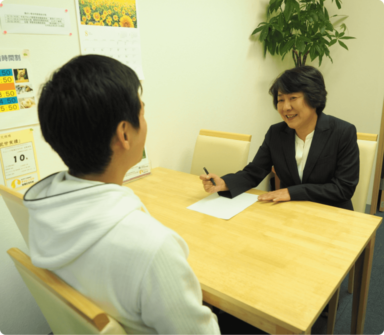 対面で面談を行う女性指導員と面談を受ける男性